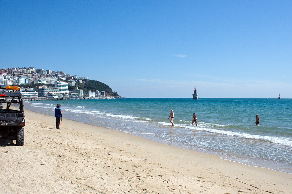 A police officer chasing bathers out of the sea. Mid-October 2018, Busan, Korea