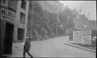 """A man walks near a poster advertising Valiquet's restaurant as """"Quebec's Best""""... / Un homme passant près d'une affiche du restaurant Valiquet's, présenté comme le « meilleur de Québec »..."""