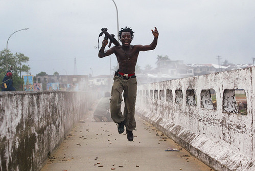 Chris Hondros. Joseph Duo, a Liberian militia commander loyal to the government, exults after firing a rocket-propelled grenade at rebel forces at a key strategic bridge in Monrovia. 2003. © Chris Hondros / Getty Images