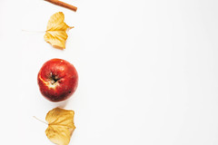 Top view of autumn concept with yellow leaves, red apple and cinnamon stick on white background.