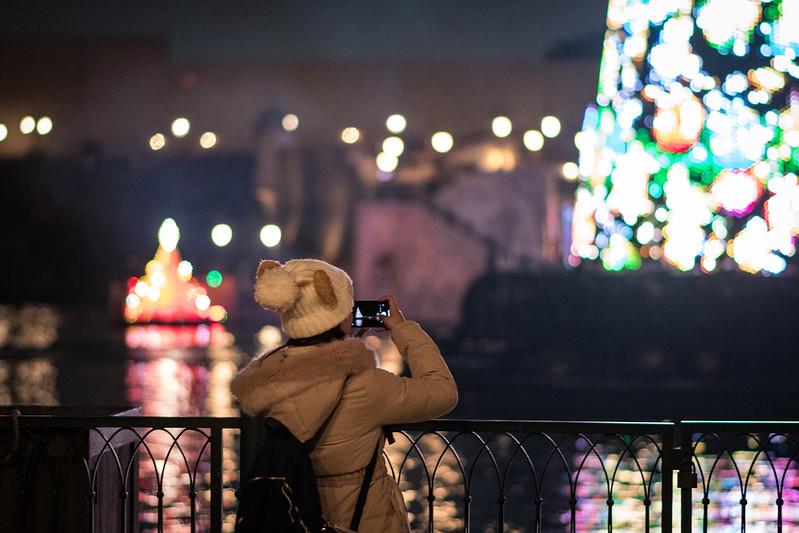 iphoneでクリスマスツリーを撮影する女性