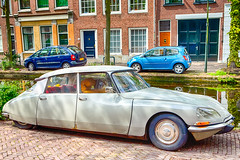 Travelling Through the Europe. Old Fashioned Retro Car in Front of Modern Cars on The Background in Small Dutch City Outdoor.