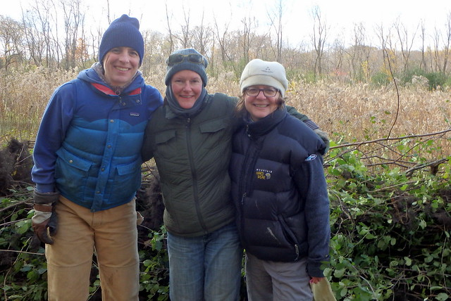 Three women posing in front of a pile of buckthorn branches.