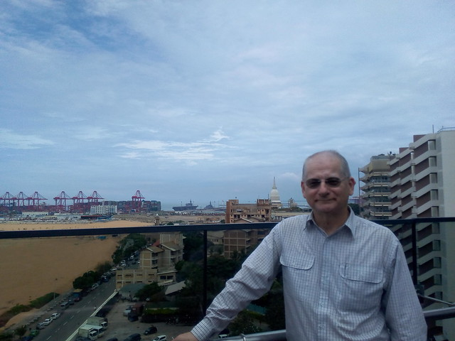 Photo from hotel roof cafe overlooking the old and new waterfront at Colombo. The grey warship at the port in the background is Japan's Kaga, a helicopter carrier.