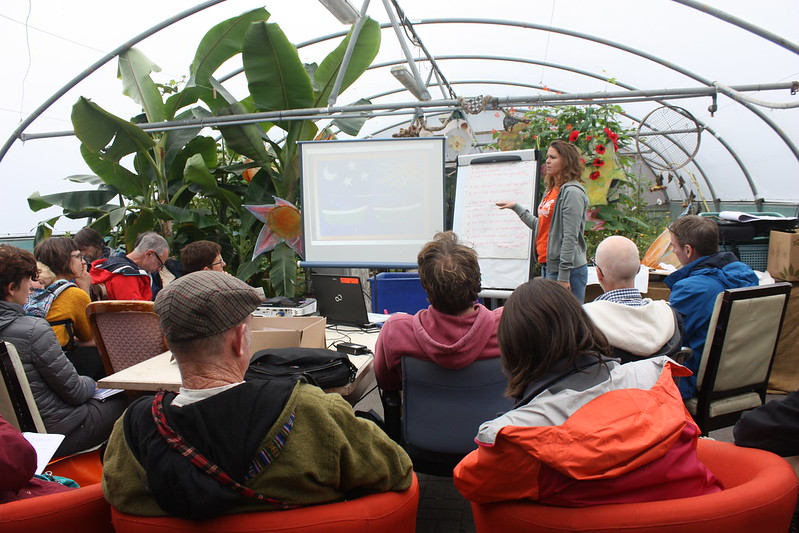 Anna Locke presenting at the national permaculture convergence 2016, in a polytunnel, a beautiful setting