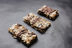 Close up of homemade muesli bars with dates and chocolate. Dark background.
