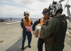 Naval Aircrewman (Helicopter) 2nd Class Ryan Quinn, right, delivers a repair part to JS Huyuga (DDH-181), Oct. 31. (U.S. Navy/MC2 Kaila V. Peters)