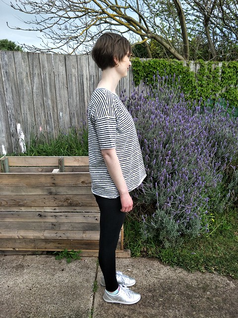 A woman stands in front of a garden fence. She wears a navy/white striped short sleeve tee with gold dots, black leggings and silver runners. Her side is to the camera.