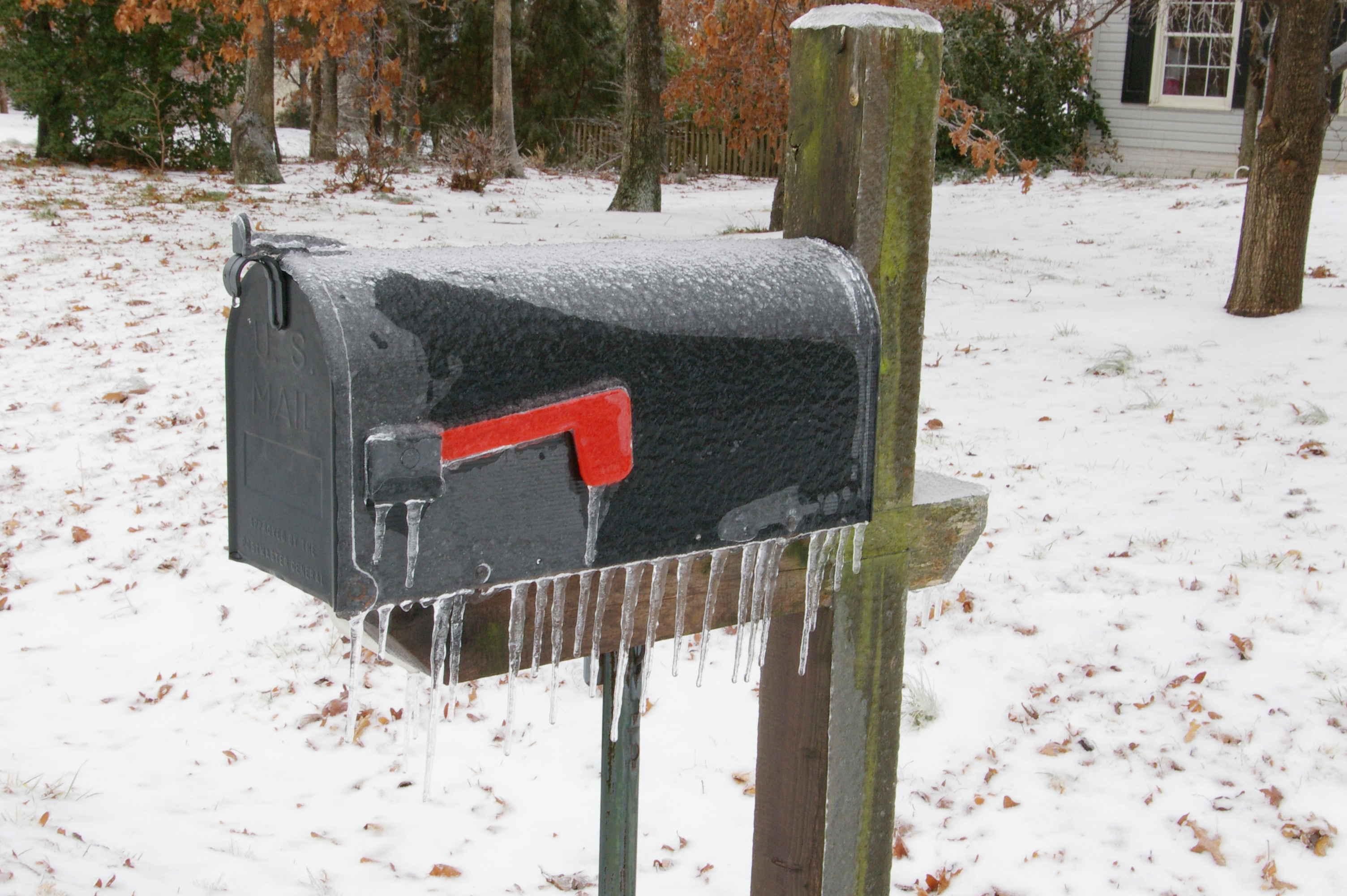 A Joroleman-style curbside mailbox with red semaphore flag. When raised, the flag indicates outgoing mail. The ice-covered mailbox was photographed in Spotsylvania County, Virginia, by Joy Schoenberger on February 14, 2007.