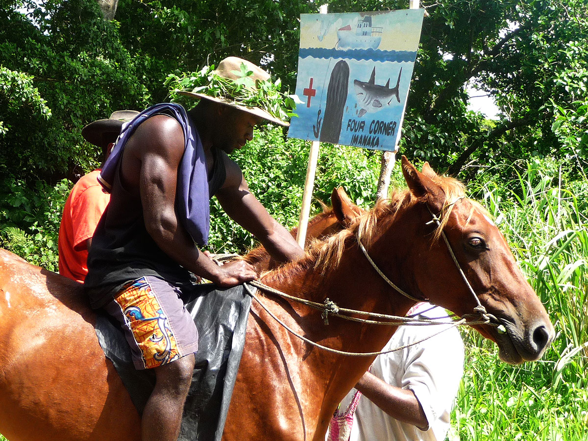 """Local Tannese Ni-Vanuatu man on horseback outside of a John Frum meeting sponsored by the """"Four Corners"""" sect that is located in Imanaka village, Tanna Island."""
