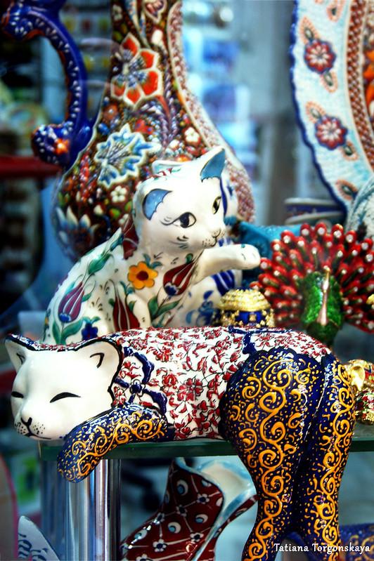Фигурки котов в витрине сувенирного магазина