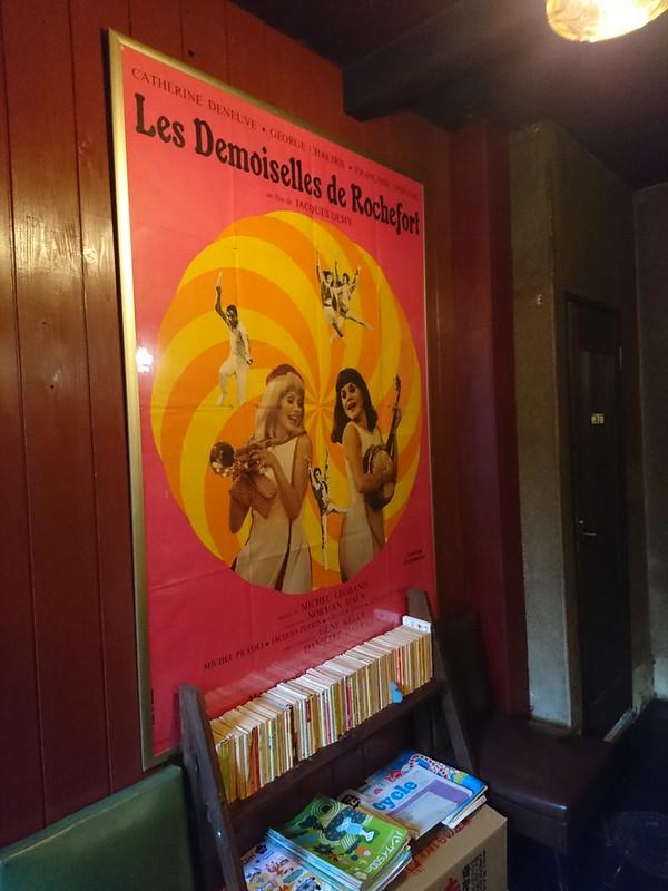 喫茶 ラ・マドラグの店内。映画「ロシュフォールの恋人たち」のポスター。カトリーヌ・ドヌーヴと姉フランソワーズ・ドルレアック主演。2018年10月18日撮影。
