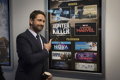 Actor Gerard Butler poses next to the movie poster for his upcoming film in the halls of the Pentagon, Oct. 15. (U.S. Navy/MC2 Paul L. Archer)