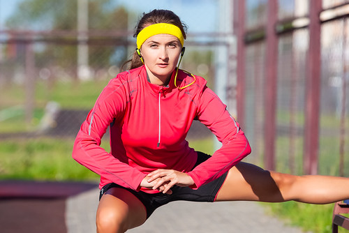 Sport Concepts. Portrait of Concentrated Caucasian Sportswoman in Outdoor Sport Outfit Having Leg Muscles Stretchings With Folded hands. Listening to Music in Headphones.
