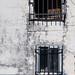 Rejas y sombras de tejas sobre fachada raída