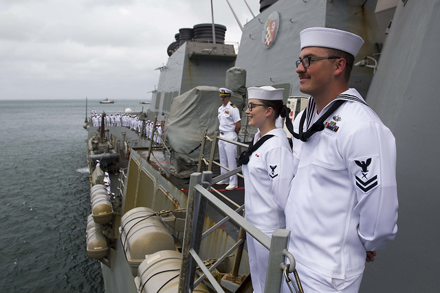 SUVA, Fiji (Oct. 14, 2018) Cryptologic Technician (Technical) 2nd Class Dylan Maynard and Cryptologic Technician (Technical) 3rd Class Natalie Maness man the rails on the weather decks of the guided-missile destroyer USS Shoup (DDG 86) while the ship pulls into the Port of Suva for a port visit. Shoup is currently participating in the Oceania Maritime Security Initiative (OMSI) program, a Secretary of Defense program leveraging Department of Defense assets transiting the region to increase the Coast Guard's maritime domain awareness, ultimately supporting its maritime law enforcement operations in Oceania. (U.S. Navy photo by Mass Communications Specialist 2nd Class William Collins III/Released)