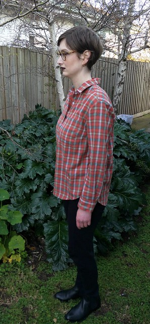 Woman stands in front of a garden fence, wearing a red check button up shirt, black pants and ankle boots. She is side on to camera.