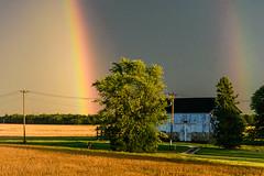 Double rainbow over cyclist and barn