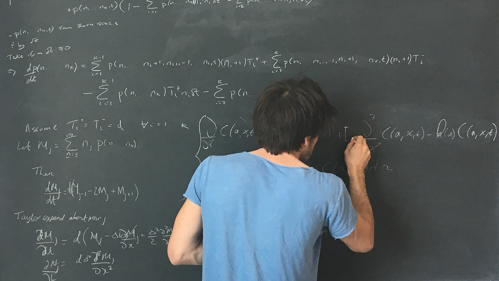 A student writing at the blackboard