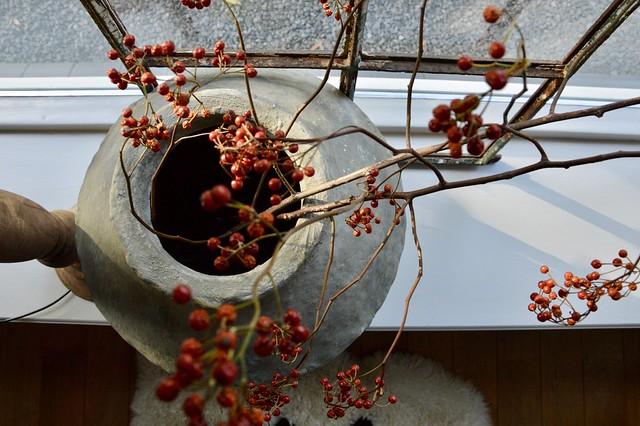 Kruik met rode bessen tak oud raam