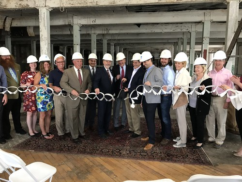 Local and state elected officials and project partners pose for a photo during an indoor ceremony at 701 River Street in Troy. Participants are wearing white hardhats and holding a string of paper collars.