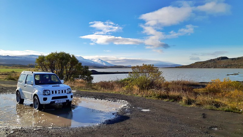 Europcar rental Jimny with lake and mountains behind