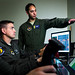Maj. Michael, a remotely piloted aircraft fundamentals course instructor pilot, right, discusses a training mission utilizing the Predator Reaper Integrated Mission Environment simulator with Tech. Sgt. Ben, an enlisted pilot student, and Staff Sgt. James, a basic sensor operator course instructor at the 558th Flying Training Squadron at Joint Base San Antonio, Texas Jul. 17, 2018. Both officer and enlisted RPA student pilots spend 85 days in the RPA Instrument Qualification course (RIQ) and 30 days in the RPA Fundamentals Course (RFC) at the 558th FTS, during the second phase of the Air Education and Training Command's RPA pilot curriculum. Last Names removed and obscured for OPSEC. (U.S. Air Force photo by J.M. Eddins Jr.)