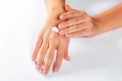 Girl spreads her hands with cream