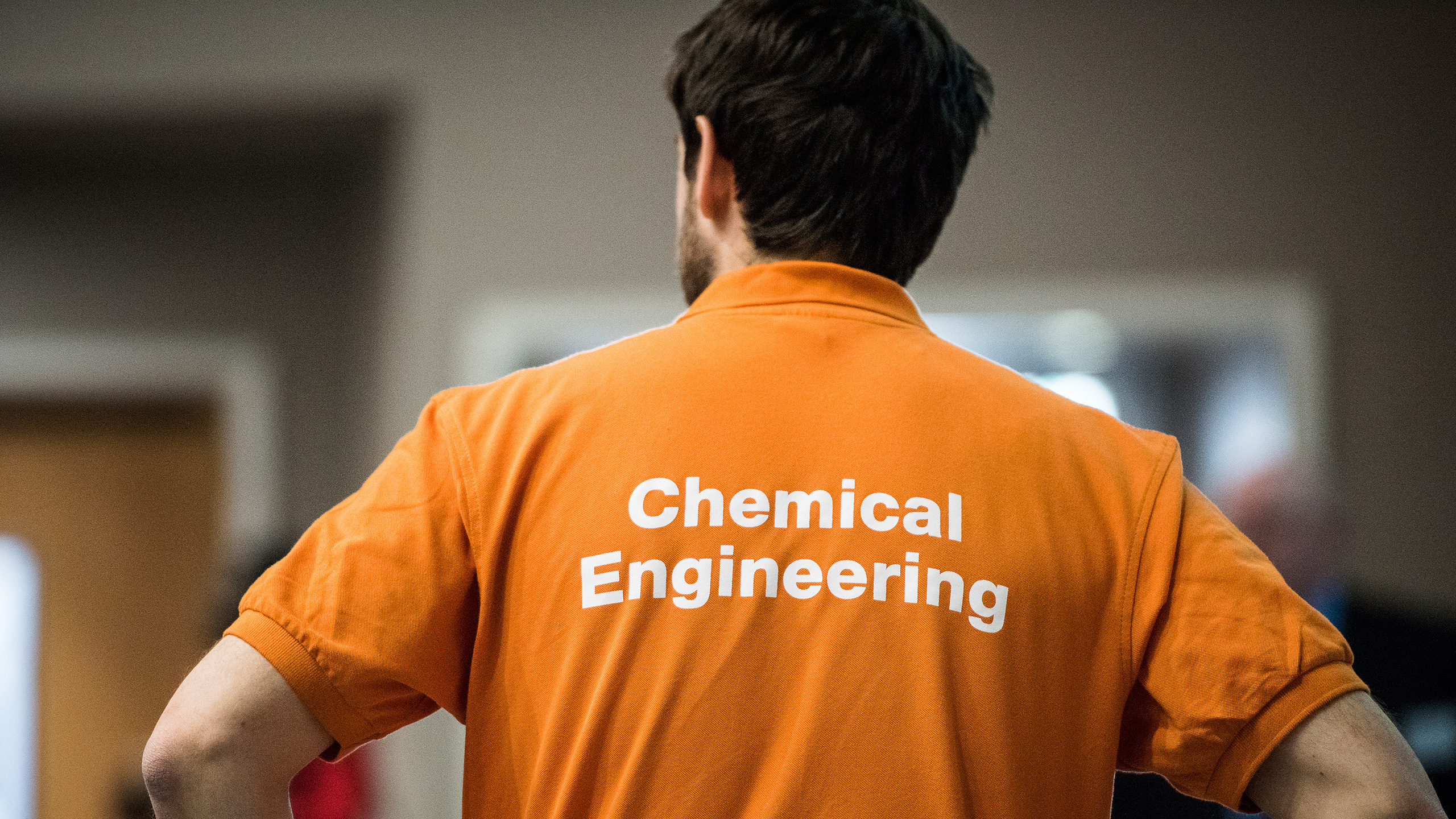 A student ambassador wearing Chemical Engineering t-shirt looking at prospective students