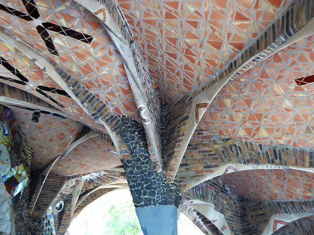 The roof of the entrance of Cripta Gaudí is inlaid with broken tiles adornment, which is a feature of  Antoni Gaudí's work