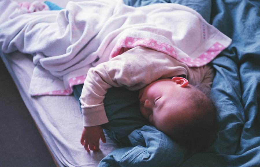 ふとんの上で昼寝する子(2のうち1)
