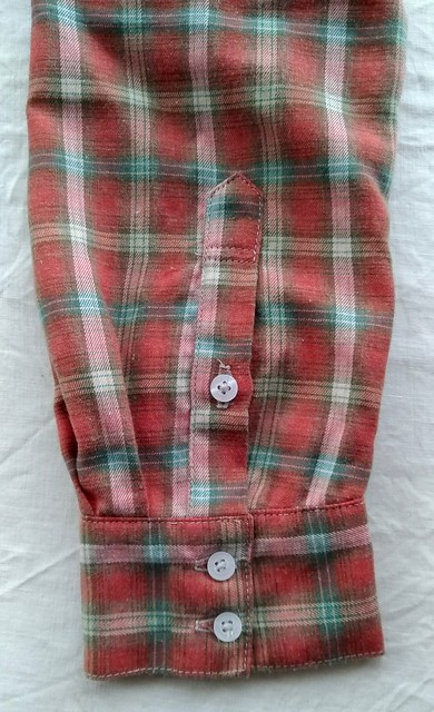 Close up of a shirt cuff and placket, sewn in a red check.