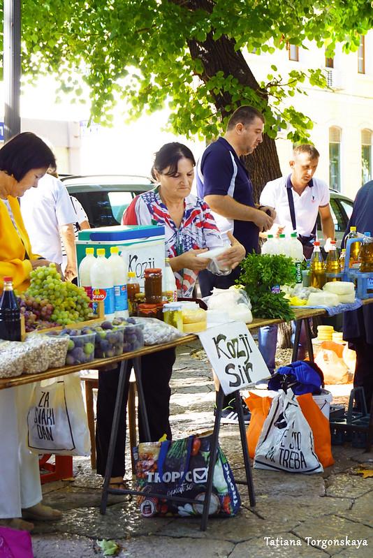 Продавцы раскладывают товары на рынке в Требине
