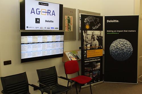 LCD obrazovky s logy partnerů, rozvrhem, roll upy Světlušky a Deloitte