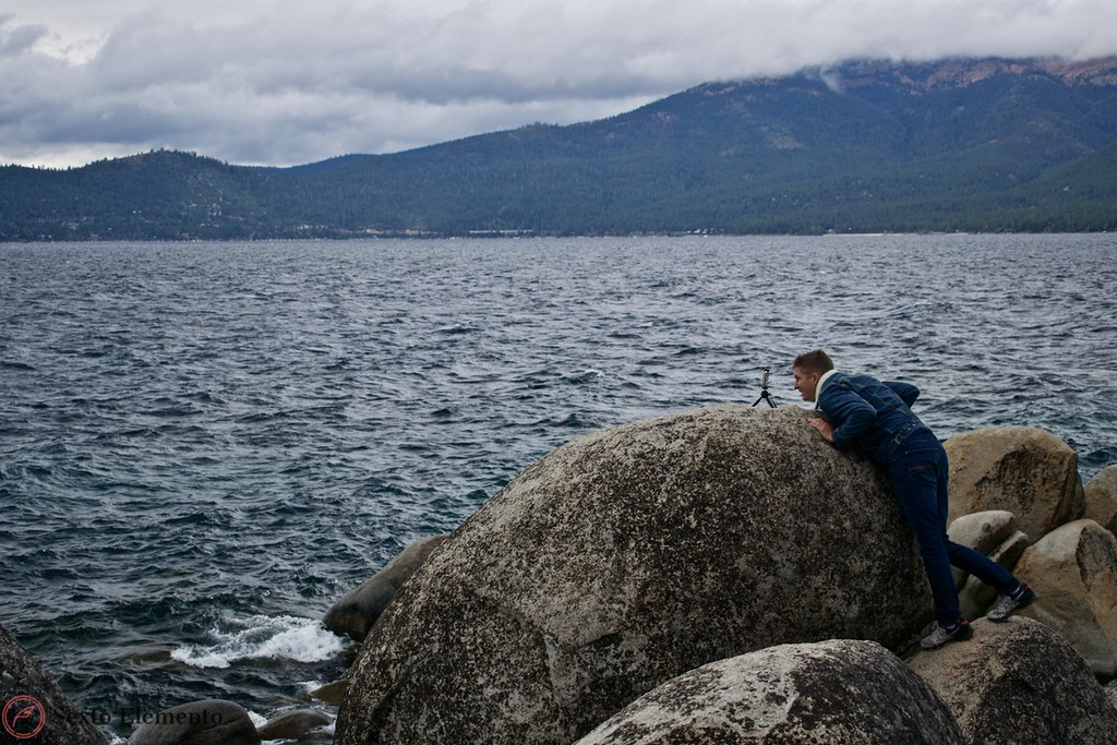 sand-harbor-person-taking-a-picture-on-a-boulder