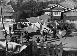 De Havilland DH60 K Moth being loaded onto a truck in a suburban street