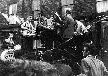 The Quarrymen performing in Rosebery Street, Liverpool on 22 June 1957. (Left to right: Hanton, Griffiths, Lennon, Garry, Shotton, and Davis). Paul McCartney can be seen in attendance (bottom right).