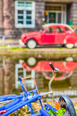 Broken and abundoned Retro Bicycle Against Red Obsolete and Old Fashioned Car on Background in Small Dutch City.
