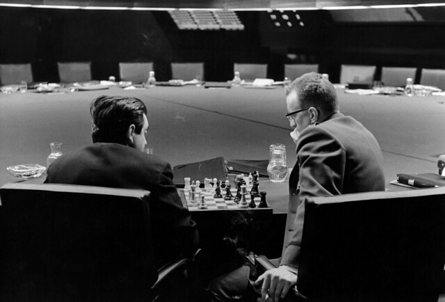 Stanley Kubrick and George C. Scott playing chess in the War Room, in a break during filming of Dr. Strangelove or: How I Learned to Stop Worrying and Love the Bomb, directed by Stanley Kubrick (1963-64; GB/United States). Production photo. © So