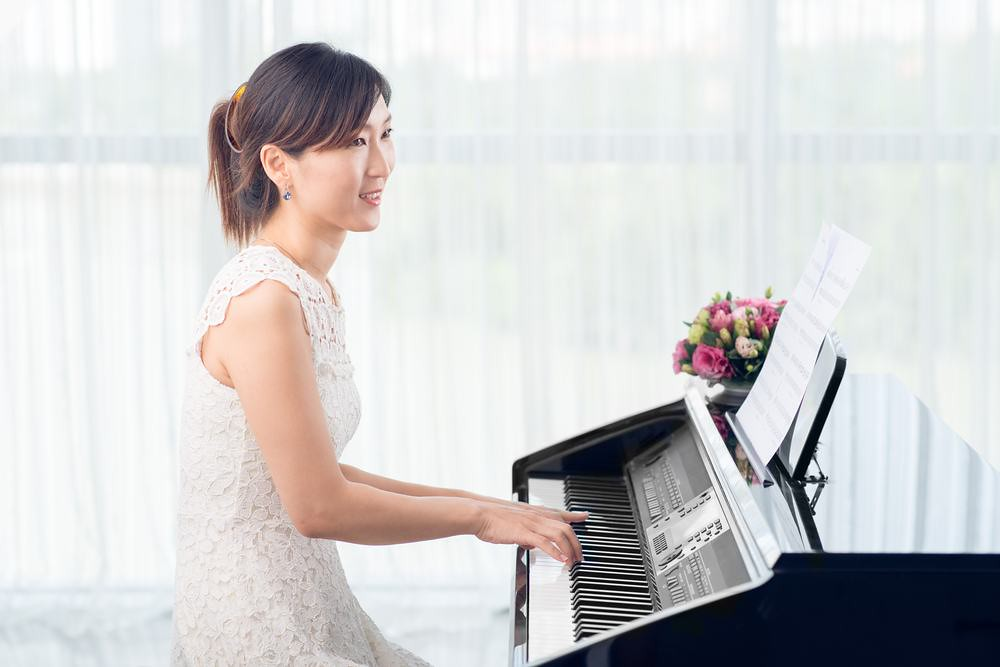photo of woman practicing piano