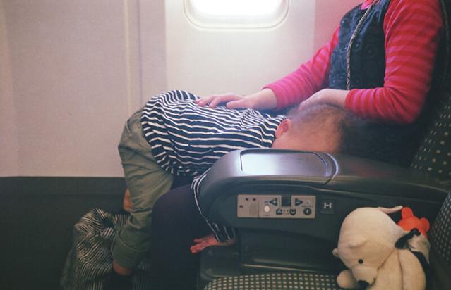 機内で奇妙な寝方をする子。