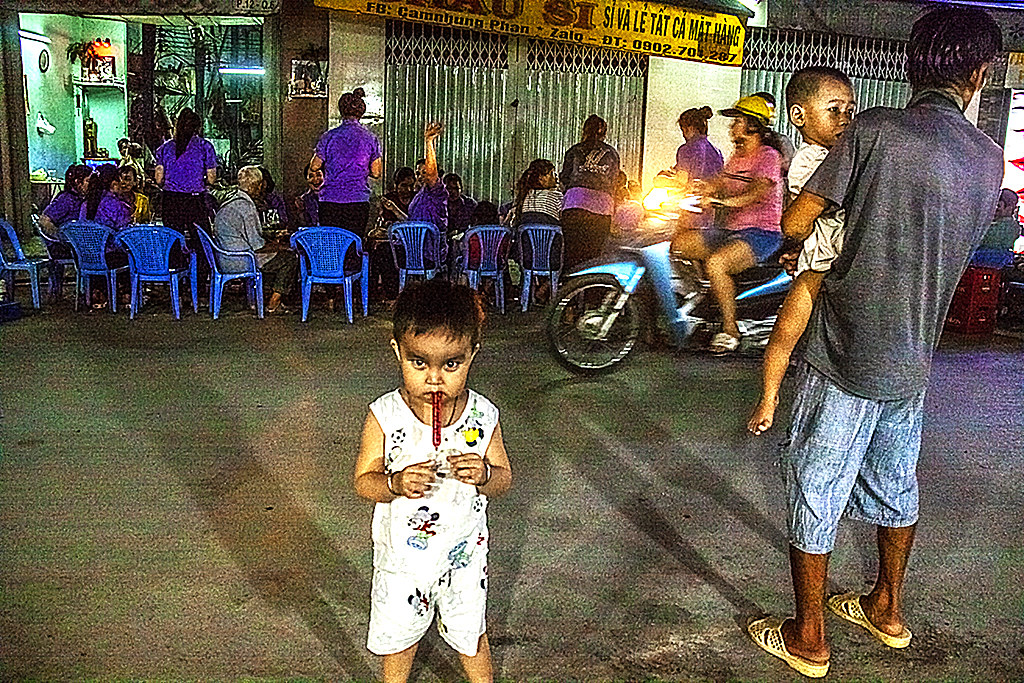 Boy in front of factory workers carousing near Phu Dinh Market--Saigon