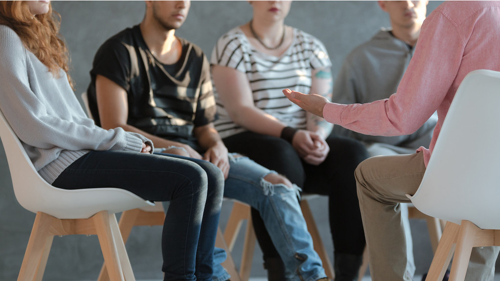 Group of young people sitting in a circle and talking to a psychologist