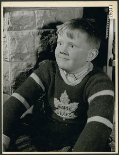 Little boy in Maple Leafs sweater listens to Miss. E. Donnelly tell a story on a Saturday at the London Public Library, Ontario /  Un petit garçon vêtu d'un chandail des Maple Leafs écoute madame E. Donnelly lors de l'heure du conte du samedi, à la b