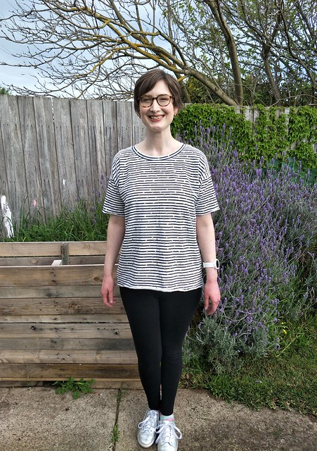 A woman stands in front of a garden fence. She wears a navy/white striped short sleeve tee with gold dots, black leggings and silver runners. She is smiling.