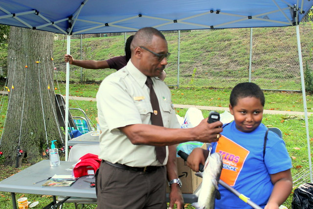 man in FWS uniform shows young man a device with fish attached