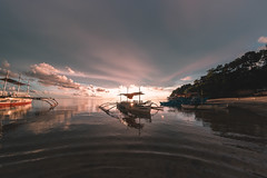 Sunset peaking behind a pumpboat in Sipalay