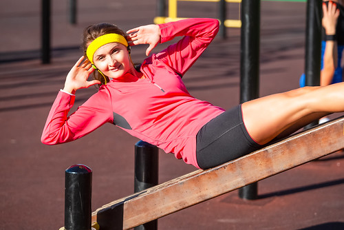 Sport Concepts. Happy Positive Caucasian Girl in Outdoor Sport Outfit Making Press-Ups on Long Bench. Listening to Music in Headphones.