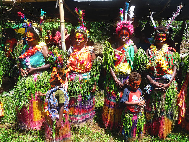 Tannese women along with little children dressed in traditional costume ready and waiting for their turn to dance in a John Frum celebration