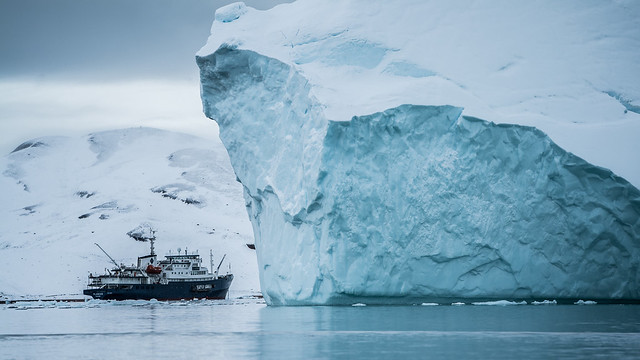 Fishing boat next to iceberg in the Arctic